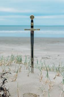 Verticale opname van een zwaard in het zandstrand