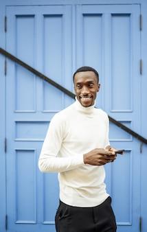 Verticale opname van een zwarte man met een coltrui die zijn telefoon vasthoudt