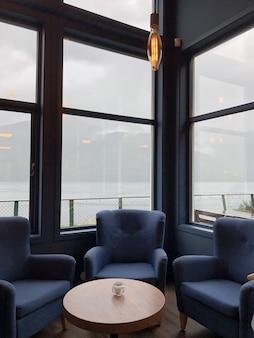 Verticale opname van fauteuils rond de tafel achter de ramen