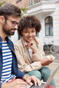 Verticale opname van geconcentreerde bebaarde man werkt samen met partner, keybroads op laptopcomputer, sandwich eten,