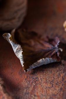 Verticale opname van gedroogde herfstbladeren op een donkerbruine tafel