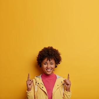 Verticale opname van gelukkig lachende vrouw met donkere huid wijst naar boven met beide wijsvingers, geeft aanbeveling of advies, stelt voor deze richting te volgen, gekleed in jas, geïsoleerd op gele muur