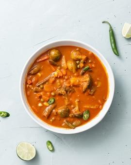 Verticale opname van groentecurry met bloemkool, bonen, maïs, pikante peper en limoen