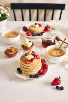 Verticale opname van heerlijke veganistische tofu pannenkoeken met kleurrijke fruit, siroop en koffie