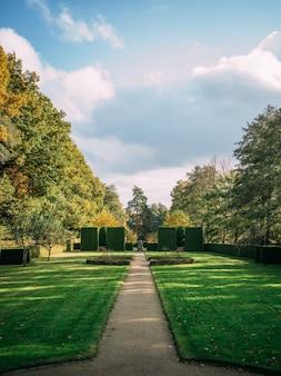 Verticale opname van het hoetger park bedekt met groen onder een bewolkte hemel in zonlicht in dortmund