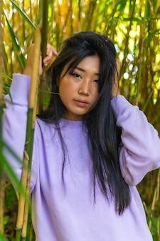 Verticale opname van het portret van een mooi chinees meisje, poserend in de buurt van bamboeplanten