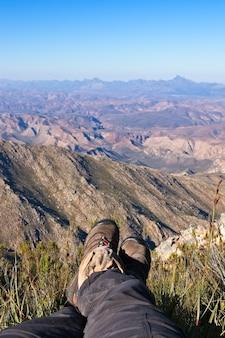 Verticale opname van iemands voeten die op de top van een heuvel boven een prachtige vallei zitten
