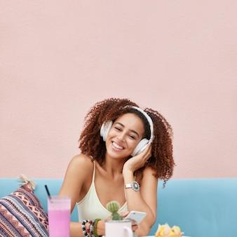 Verticale opname van mooie vrouwelijke meloman heeft een donkere huid en een gelukkige uitdrukking, luistert naar favoriete muziek in de koptelefoon, geniet van smoothie