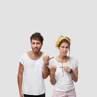 Verticale opname van ontevreden europese vrouwelijke en mannelijke volwassenen die naar elkaar wijzen, negatieve emoties uiten, zich depressief voelen, dicht bij elkaar staan, geen huishoudelijk werk willen doen