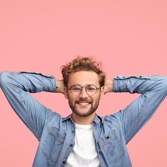 Verticale opname van ontspannen, zorgeloze man houdt de handen achter het hoofd, heeft een positieve uitdrukking, lacht aangenaam, luistert iets met belangstelling, gekleed in een modieus shirt, geïsoleerd over roze muur