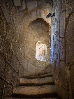 Verticale opname van smalle trappen in een stenen toren met een klein raam