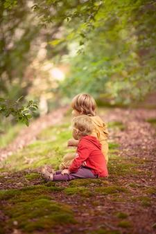 Verticale opname van twee kinderen die op een heuvel zitten en naar het uitzicht kijken