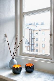 Verticale opname van twee unieke kandelaars en een vaas met een kamerplant bij het raam