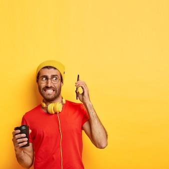 Verticale opname van verbaasde nerveuze man vermijdt praten over smartphone