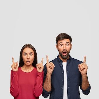 Verticale opname van verbijsterde collega's wijzen met wijsvingers naar boven, tonen vrije ruimte voor uw advertentie, hebben ogen vol ongeloof