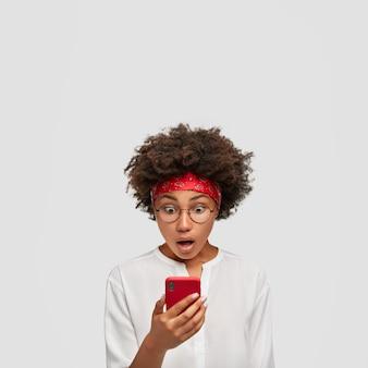 Verticale opname van verrast donkere huid jonge ontvangt bericht op mobiele telefoon, staart met onverwachte blik op het scherm
