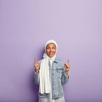 Verticale opname van vrolijk geïnspireerde vrouw wijst wijsvinger naar boven, heeft een aangename glimlach, toont lege ruimte, draagt witte sluier volgens tradities, geïsoleerd over paarse muur met vrije ruimte