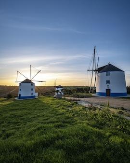 Verticale opname van windmolens met een zonsopgang in een heldere blauwe lucht op de achtergrond