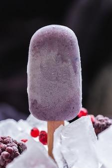 Verticale opname van zelfgemaakt veganistisch ijs bedekt met chocolade en omgeven door ijsblokjes