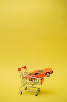 Verticale oriëntatie. metalen kar met een oranje auto op een gele geïsoleerde achtergrond met ruimte voor tekst