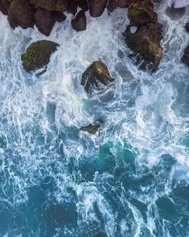 Verticale overhead luchtfoto van een golvende blauwe zee tegen de rotsen