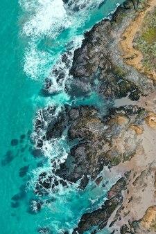 Verticale overhead schot van de prachtige kustlijn van de zee met blauw schoon water en zandstrand