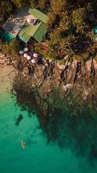 Verticale overheadfoto van een zee met bomen en huizen aan de kust