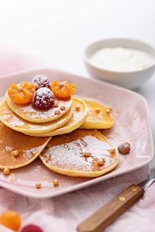 Verticale pannenkoeken met frambozen, physalis, hazelnoot en ahornsiroop op roze bord, bestrooid met poedersuiker, met vork en zure room op roze keukenpapier