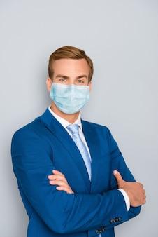 Verticale portret van aantrekkelijke gezonde inhoud stijlvolle man dragen blauwe katoenen masker gevouwen armen ncov mers infectie veiligheidsmaatregelen pandemie geïsoleerd op grijze kleur achtergrond