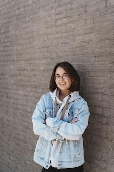Verticale portret van een aantrekkelijk jong meisje met kort haar, bril en streetstyle kleding, leunend op een bakstenen muur.