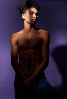 Verticale portret van een jonge man die in een casual pose staat in de schaduw, gespierde transgender man