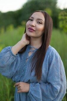 Verticale portret van een mooie jonge vrouw in een veld. meisje in oren van tarwe op een hete zomer veld buitenshuis.