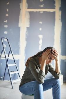 Verticale portret van gefrustreerde jonge vrouw verwoest door renovaties project zittend op verf kan tegen droge muur, ruimte kopiëren