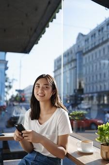 Verticale portret van gelukkig lachend meisje zit in café met mobiele telefoon in de buurt van raam, koffie drinken.