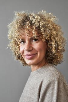 Verticale portret van glimlachende vrouw met krullend haar terwijl poseren tegen een grijze achtergrond, uniek schoonheidsconcept