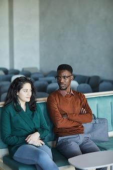 Verticale portret van jonge afro-amerikaanse man zit met midden-oosterse vrouw zittend op stoelen in auditorium tijdens het wachten op seminar of klas, kopie ruimte