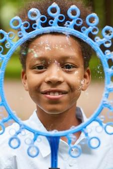 Verticale portret van lachende afro-amerikaanse jongen kijkt door grote bellenblaas toverstaf tijdens het spelen buiten in het park