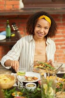 Verticale portret van lachende afro-amerikaanse vrouw genieten van diner met vrienden en familie buiten op zomerfeest