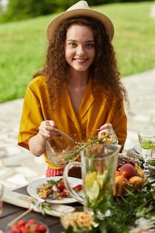 Verticale portret van lachende jonge vrouw genieten van diner met vrienden en familie buiten op zomerfeest