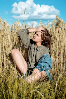 Verticale portret van mooie jonge vrouw in het veld. meisje in oren van tarwe op hete zomer veld buitenshuis, mode en model tiener.