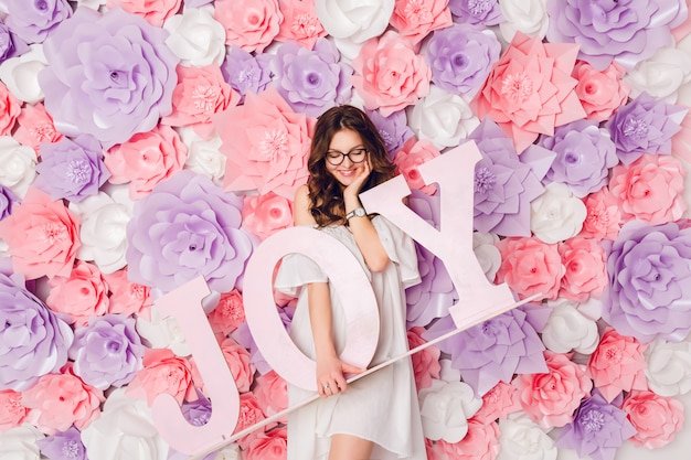 Verticale portret van schattig brunette meisje. ze staat op en houdt het houten woord joy breed glimlachend vast. achtergrond in roze bloemen