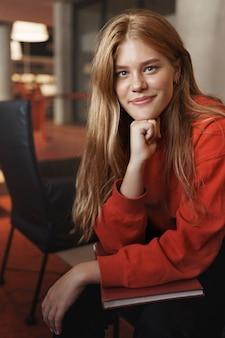 Verticale portret van slimme mooie roodharige meisje, glimlachend als zittend op een fauteuil en magere arm.