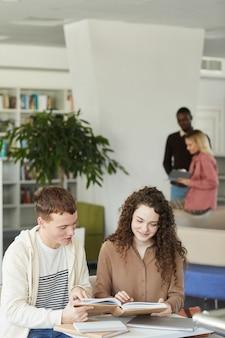 Verticale portret van twee jonge studenten jongen advertentie meisje samen studeren zittend aan tafel in de universiteitsbibliotheek en glimlachen
