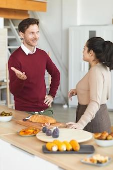 Verticale portret van volwassen man en vrouw chatten tijdens etentje binnenshuis met vrienden