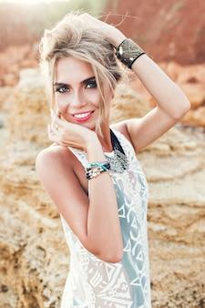 Verticale portret van vrij blond meisje lachend naar de camera op verlaten strand. ze houdt haar boven en ziet er gelukkig uit.