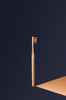Verticale regenboog houten tandenborstel in het midden van het beeld met donkerblauwe muur met oranje schaduweffect geprojecteerd naar rechts