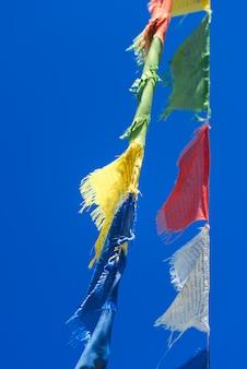 Verticale rijen van kleurrijke tibetaans boeddhistische gebedsvlaggen zwaaien