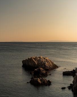 Verticale schot van rotsen van verschillende grootte in de zee onder de heldere hemel