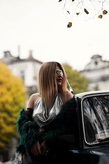 Verticale selectieve opname van een aantrekkelijk stijlvol en modieus vrouwelijk model in een jurk in de buurt van een auto