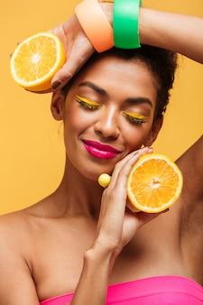 Verticale sensuele afro-amerikaanse vrouw met gesloten ogen met twee delen van sinaasappel en genieten van citrusvruchten geïsoleerd, over gele muur
